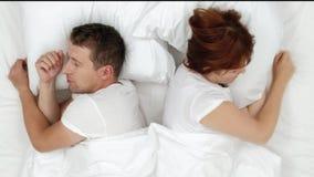 Der schnarchende Mann, der heraus lautes erdrosseln, seine Frau oben während der lauten Nacht aufweckend und sie schließen Ohren  stock footage