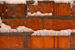 Der Schnee auf der Oberfläche einer Backsteinmauer als Hintergrund stockfotografie