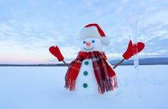 Der Schneemann im Plaidschal, roter Hut, Handschuhe Erstaunlicher Sonnenaufgang erleuchten den Himmel Nette Landschaft mit den Be lizenzfreies stockfoto