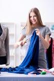 Der Schneider der jungen Frau, der im Seminar über neues Kleid arbeitet Lizenzfreies Stockbild