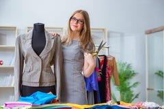 Der Schneider der jungen Frau, der im Seminar über neues Kleid arbeitet Stockbilder