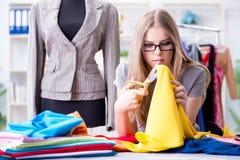 Der Schneider der jungen Frau, der im Seminar über neues Kleid arbeitet Stockfoto