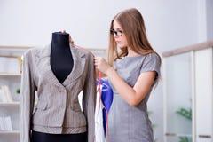 Der Schneider der jungen Frau, der im Seminar über neues Kleid arbeitet Stockbild