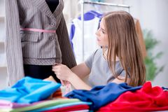 Der Schneider der jungen Frau, der im Seminar über neues Kleid arbeitet Lizenzfreie Stockfotos