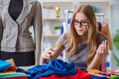 Der Schneider der jungen Frau, der im Seminar über neues Kleid arbeitet Lizenzfreies Stockfoto