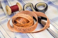 Der Schneider ` s Maßband, eine hölzerne Spule des Threads und Damenschneiderinnen scissors auf Gewebehintergrund Stockfotografie