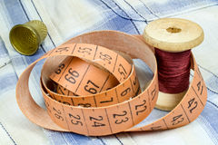 Der Schneider ` s Maßband, eine hölzerne Spule des Threads und Muffe auf dem Gewebe Lizenzfreies Stockbild