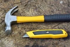 Der Schneider und der Hammer auf hölzernem Hintergrund Lizenzfreies Stockbild