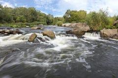 Der schnelle Fluss des Flusses, der felsigen Küsten, der Stromschnellen, der hellgrünen Vegetation und des bewölkten blauen Himme Lizenzfreie Stockbilder