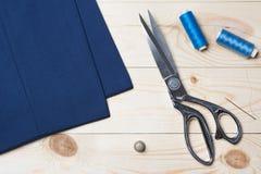 Der Schnitt des blauen Gewebes mit einem Taylor scissors auf Holztisch stockfotos