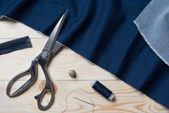 Der Schnitt des blauen Gewebes mit einem Taylor scissors auf Holztisch stockbilder
