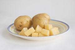 Der Schnitt und die vollständige Kartoffel auf einer Platte Stockfotografie