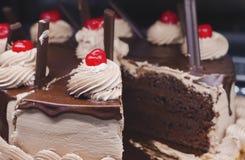 Der Schokoladenschwammkuchen, der mit verziert wird, sahnt und Kirschen lizenzfreie stockfotos