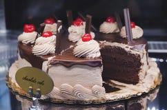 Der Schokoladenschwammkuchen, der mit verziert wird, sahnt und Kirschen stockbild