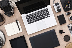 Der Schreibtisch des Designers mit offenen Laptop-, Tabletten- und Weinlesekameras Direkt oben stockfotografie
