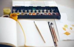 Der Schreibtisch des Künstlers auf welchem Sketchbook, Bürsten, Aquarell und Gouachefarben stockfoto
