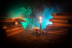 Der Schreibtisch des Zauberers Ein Schreibtisch beleuchtet durch Kerzenlicht Ein menschlicher Schädel, alte Bücher auf Sand tauch Lizenzfreie Stockfotos