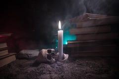 Der Schreibtisch des Zauberers Ein Schreibtisch beleuchtet durch Kerzenlicht Ein menschlicher Schädel, alte Bücher auf Sand tauch Stockbilder