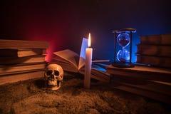 Der Schreibtisch des Zauberers Ein Schreibtisch beleuchtet durch Kerzenlicht Ein menschlicher Schädel, alte Bücher auf Sand tauch Stockbild