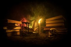 Der Schreibtisch des Zauberers Ein Schreibtisch beleuchtet durch Kerzenlicht Ein menschlicher Schädel, alte Bücher auf Sand tauch Lizenzfreies Stockbild