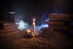 Der Schreibtisch des Zauberers Ein Schreibtisch beleuchtet durch Kerzenlicht Ein menschlicher Schädel, alte Bücher auf Sand tauch Stockfotografie