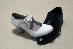 Der Schuh der weißen Frau über dem Schuh der schwarzen Männer lizenzfreie stockfotos