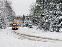 Der Schulbus, der hinunter einen Schnee fährt, bedeckte Landstraße - 1 stockbild