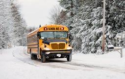 Der Schulbus, der hinunter einen Schnee fährt, bedeckte Landstraße - 3 Lizenzfreies Stockbild