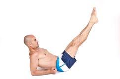 Der schulterfreie Mann, der sich aus den Grund tut untere ABS hinlegt, trainieren, indem er seine Beine anhebt. Stockfotos
