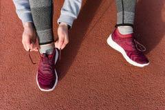Der Schuss der athletischen Frau binden ist sie Spitzee vor einem Lauf stockfotografie
