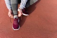Der Schuss der athletischen Frau binden ist sie Spitzee vor einem Lauf stockfotos