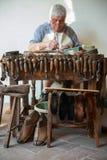 Der Schuster repariert einen Schuh an seiner Werkbank Stockfotografie