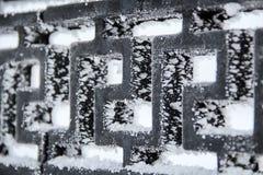 Der schwarze Metallzaun, bedeckt mit Eiskristallen Stockbilder
