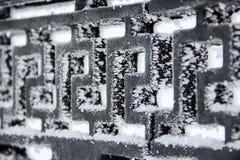 Der schwarze Metallzaun, bedeckt mit Eiskristallen Stockfoto