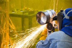 Der Schweißenshandwerker, der das Stahlrohr reibt Stockbild