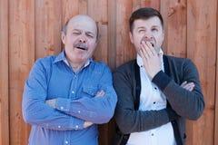 Der Schwiegervater und der Schwiegersohn, welche die hölzerne Wand bereitstehen stockfotos