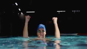 Der Schwimmer, der oben springt und Arme im Pool anhebend zujubelt stock video footage