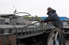 Der Seemann wirft das Liegeplatzende von der Schiff ` s Seite auf den Schiffspoller Lizenzfreie Stockbilder