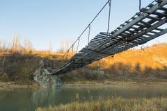 Der sehr alte hängende Steg über einem kleinen Fluss Lizenzfreie Stockfotos