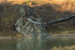 Der sehr alte hängende Steg über einem kleinen Fluss Stockfoto