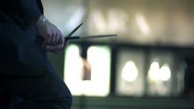 Der Seitenschuß des Mannes klopfend mit Trommel haftet auf seinen Schenkeln im slowmo stock footage