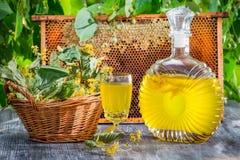 Der selbst gemachte Likör, der vom Honig gemacht werden und der Kalk im Sommer arbeiten im Garten Stockbilder
