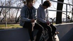 Der Skateboardfahrer mit zwei Freunden und bmx Reiter sitzen zusammen auf hohem Geländer im Stadtrochenpark unter Verwendung ihre stock video