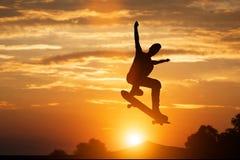 Der Skateboardfahrer springend bei Sonnenuntergang Stockbild
