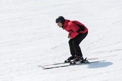Der Skifahrer, der unten die Steigung ohne Ski kommt, haftet Stockfotografie