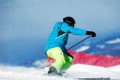Der Skifahrer im Matrosen und in den gelben Spitzen steigt dynamisch auf den Steigungen ab lizenzfreies stockfoto