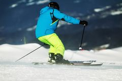 Der Skifahrer im Matrosen und in den gelben Spitzen steigt dynamisch auf den Steigungen ab stockfotografie