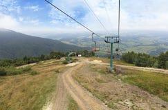 Der Skilift trägt Touristen und Gepäck auf und ab die Berge Lizenzfreie Stockbilder