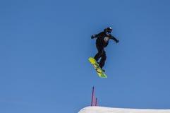 Der Snowboarder, der Läufe genießen und die Sprünge auf Frühling ` s dauern Schnee lizenzfreie stockfotos