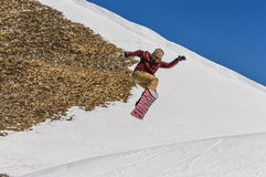 Der Snowboarder, der Läufe genießen und die Sprünge auf Frühling ` s dauern Schnee Lizenzfreie Stockfotografie